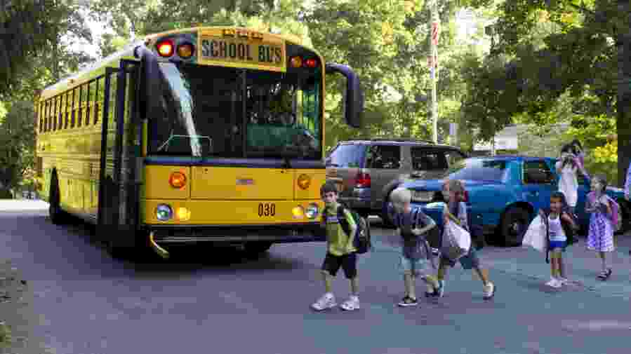A group of second graders getting on a school bus for the first day of school