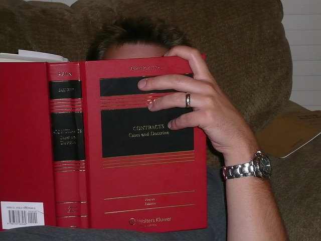 Photo of a person reading a Contracts legal textbook
