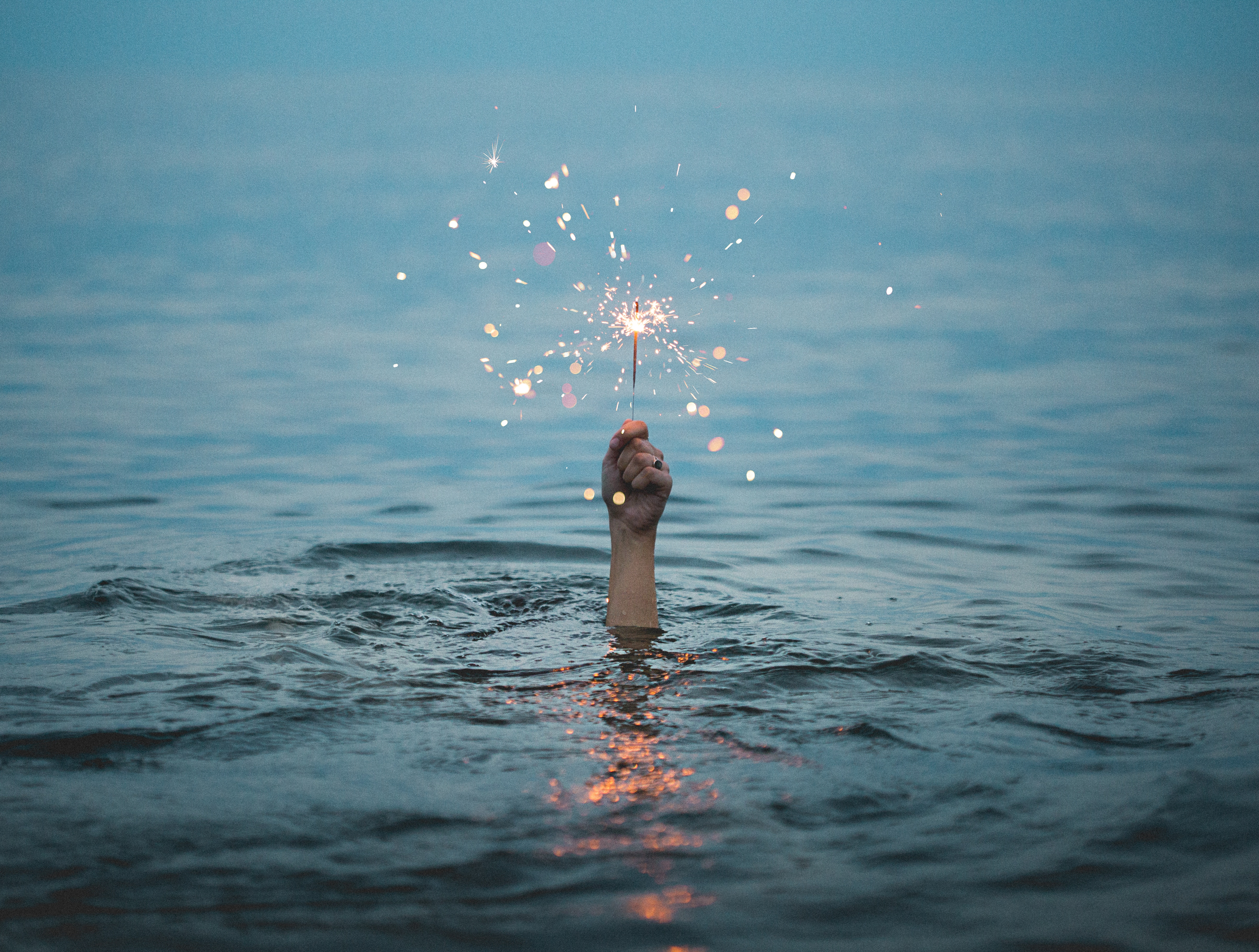 Photo showing a hand sticking above the surface of water, holding a lit sparkler