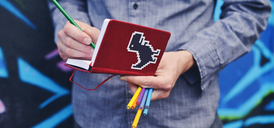 Photo of a person holding a notebook with a Tyrannosaurus Rex sticker and some colored pencils